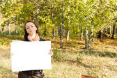 Woman in the countryside holding a card — Stock Photo