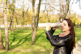 Woman using a rolled newspaper as a spyglass — Stock Photo