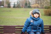 Ragazzo seduto su una panchina nel giardino — Foto Stock