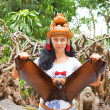 Woman in headdress holding a flying fox — Stock Photo #15859731