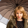 Stock Photo: Smiling blonde teenager under umbrella