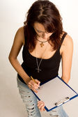 Young student writing on a clipboard — Stock Photo
