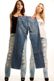 Two girls holding up a pair of jeans — Stock Photo