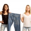 Two sexy friends posing with a pair of jeans — Stock Photo