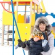 Happy mother and son in winter outfits waving — Stock Photo