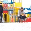 Young family out toboganning in snow - Stock Photo