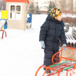 Stock Photo: Little boy with his sled in winter snow
