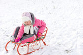 Little girl riding a toboggan in snow — Stock Photo