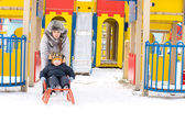 Mum giving her young son a toboggan ride — Stock Photo