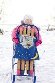 Merry little girl holding her winter sled — Stock Photo