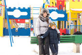 Mother and son in a snowy childrens playground — Foto de Stock