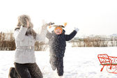Mother and son frolicking in the snow — ストック写真