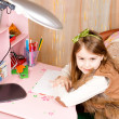 Smiling pretty little girl at her desk — Foto Stock