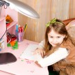 Smiling pretty little girl at her desk — Stockfoto