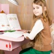 Smiling young girl working at her desk — Stock Photo
