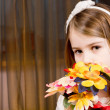 Stock Photo: Shy little girl with a bouquet of flowers