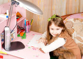 Smiling pretty little girl at her desk — Stock Photo