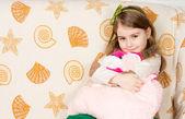 Usměvavá holčička objímání její oblíbená hračka — Stock fotografie