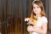 Pretty little girl holding flowers — Stock Photo