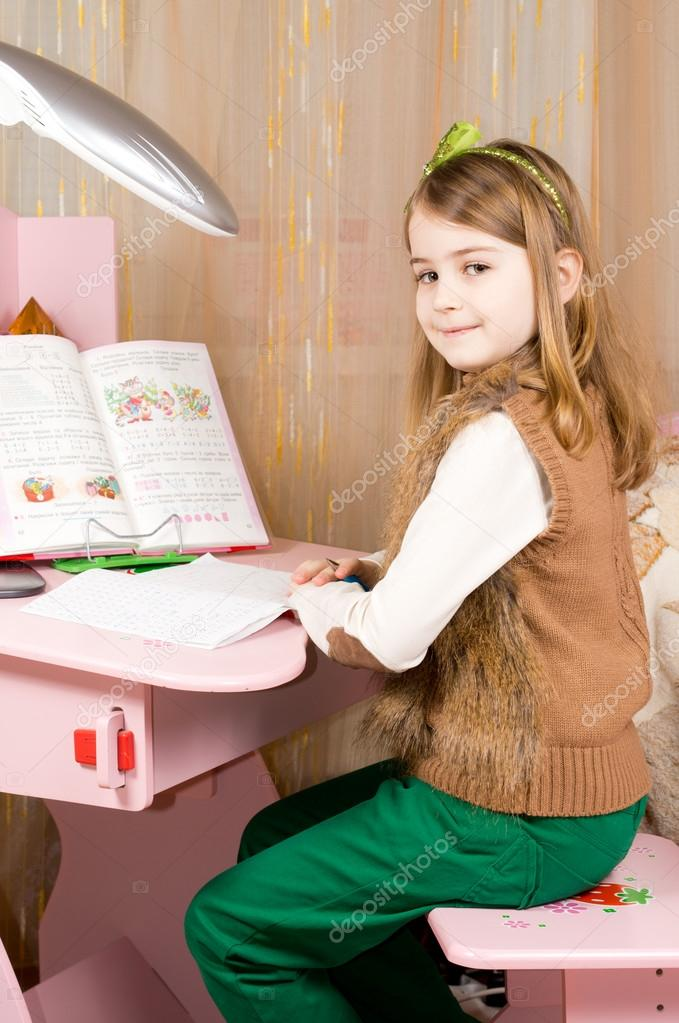 Beautiful smiling young girl sitting working at her pink desk in her bedroom doing her homework for school  Stock Photo #20009609