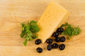 Cheese served with black olives — Stock Photo