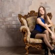 Attractive woman posing in an antique armchair — Stock Photo