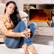 Casual woman relaxing in the warmth of a fire — Stock Photo