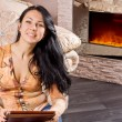 Smiling beautiful woman in front of a fire — Stock Photo