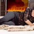 Glamorous woman lying in front of a fire — Stock Photo #22245863
