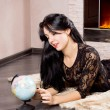 Beautiful woman playing with a globe — Stock Photo