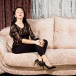 Sophisticated woman posing on a sofa — Stock Photo