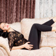 Stylish woman relaxing on a sofa — Stock Photo