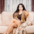 Glamorous woman posing in a fur coat - Stock Photo