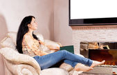 Woman daydreaming in front of the fire — Stock Photo