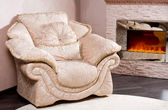Comfortable armchair near a blazing fire — Stock Photo