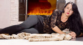 Glamorous woman lying in front of a fire — Stock Photo
