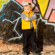 Stock Photo: Confident little boy posing in front of graffiti
