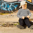 Sulking little boy sitting on a sidewalk — Stock Photo