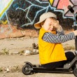 Tearful young boy sitting on his scooter — Stock Photo #24405851
