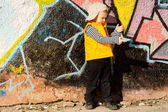 Young boy playing in front of colourful graffiti — Stock Photo