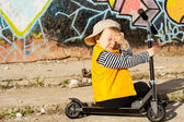 Tearful young boy sitting on his scooter — Stock Photo