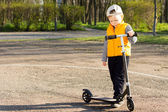 Handsome little boy with his scooter — Stock Photo