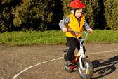 Cute young boy practising riding his bike — Stock Photo