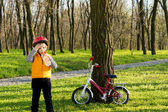 Cute child out cycling drinking bottled water — Stock Photo