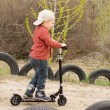 Little boy riding his scooter on dirt lane — Stock Photo #24591861