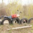 Young boy lying on old tyres — Stockfoto