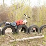 古いタイヤの上に横たわる少年 — ストック写真