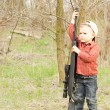Small boy holding up a large rifle — Stock Photo