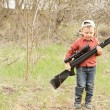 Foto Stock: Small boy carrying rifle