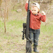 Foto Stock: Small boy holding large rifle